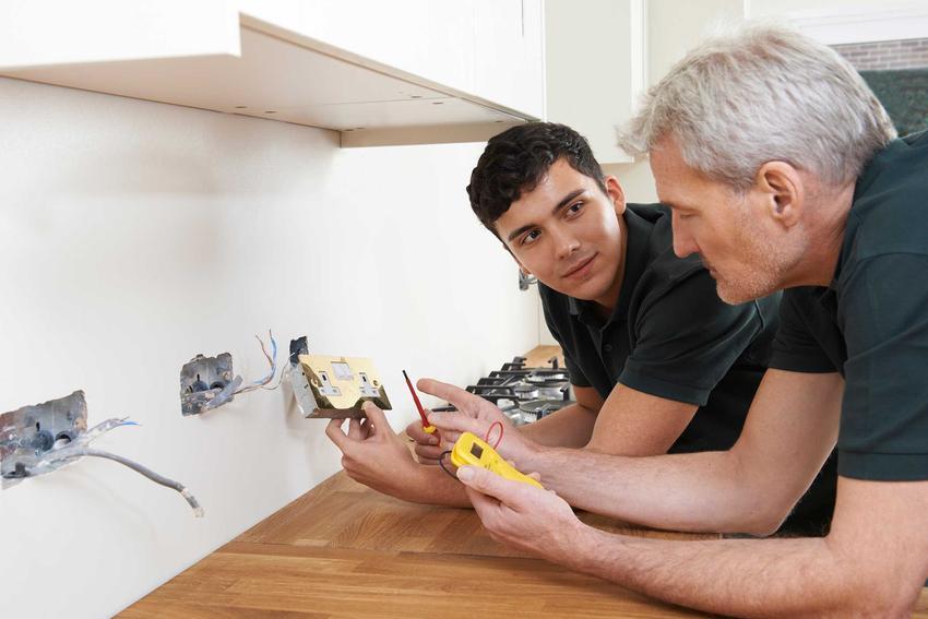 Dwóch mężczyzn montujących gniazdka w kuchni nad blatem, a także jak rozmieścić gniazdka w kuchni krok po kroku