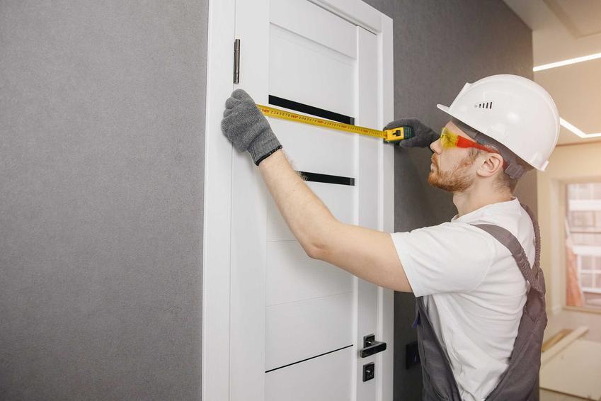 Mężczyzna mierzący nietypowy wymiar drzwi wewnętrzne, a także standardowe i nietypowe wymiary drzwi wewnętrznych krok po kroku