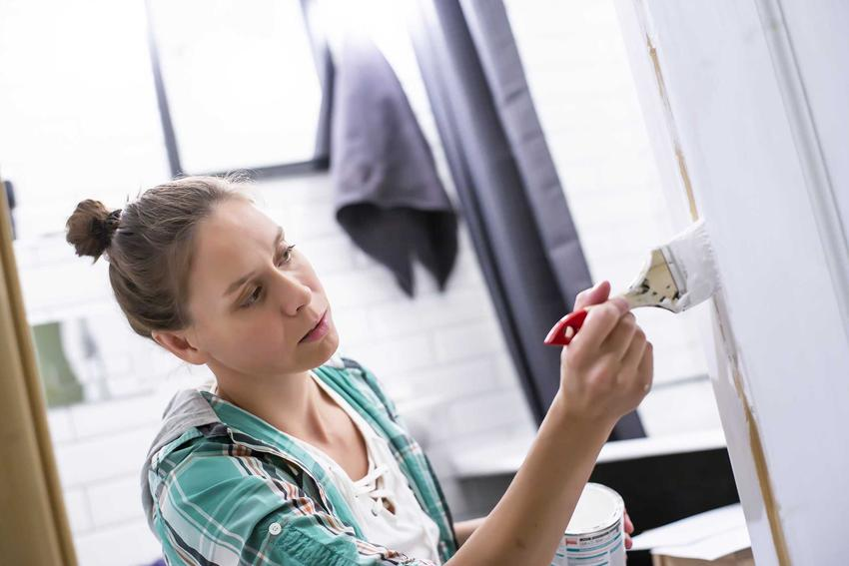 Kobieta malująca pędzelkiem detale w łazience, czyli malowanie łazienki krok po kroku, najlepsze farby, porady i wybór farb