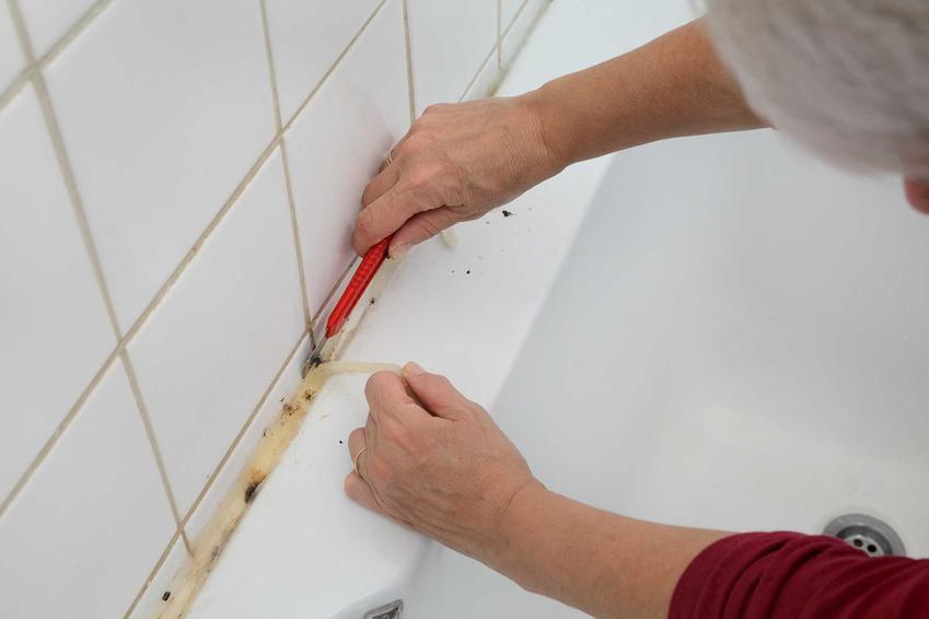 Kobieta usuwająca silikon z wanny za pomocą nożyka, a także skuteczny środek do usuwania silikonu, dobre preparaty, marki, ceny i porady
