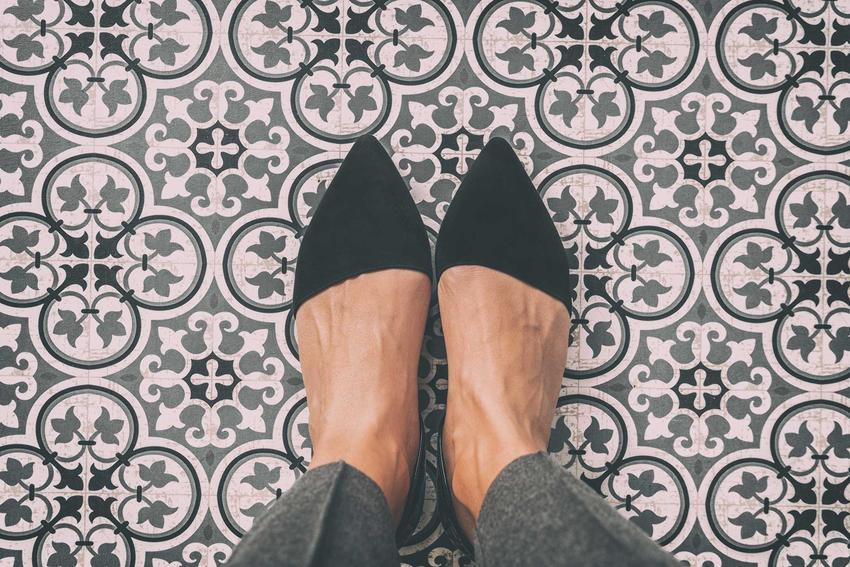 Kobieta w eleganckich butach stojąca na podłodze z płytkami, a także klasa ścieralności gresu krok po kroku, czyli stopień wytrzymałości powierzchni