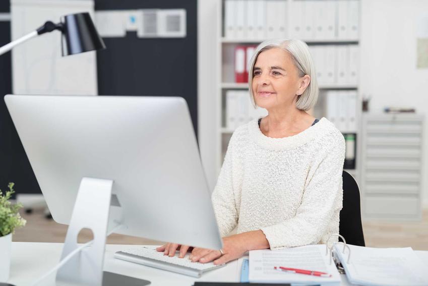 Kobieta przed wiekiem emerytalnym pracująca przy komputerze, a także okres ochronny przed emeryturą, czyli ochrona przedemerytalna krok po kroku