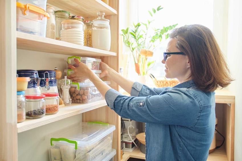 Kobieta układająca słoiki na spiżarni w kuchni, a także projekty, aranżacje, wyposażenie, podpowiedzi i porady