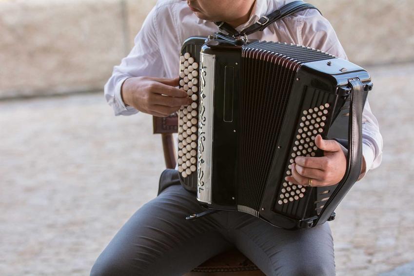 Mężczyzna grający na małym guzikowym akordeonie basowym, a także cena akordeonu i ile kosztują używane i nowe akordeony