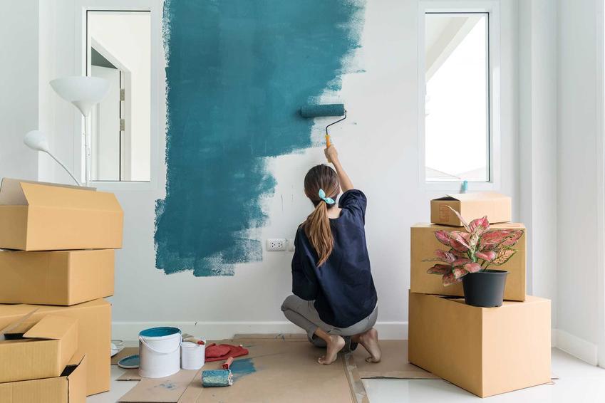 Kobieta malująca pokój na granatowo, a także podpowiedzi, jak pomalować pokój krok po kroku, praktyczne porady