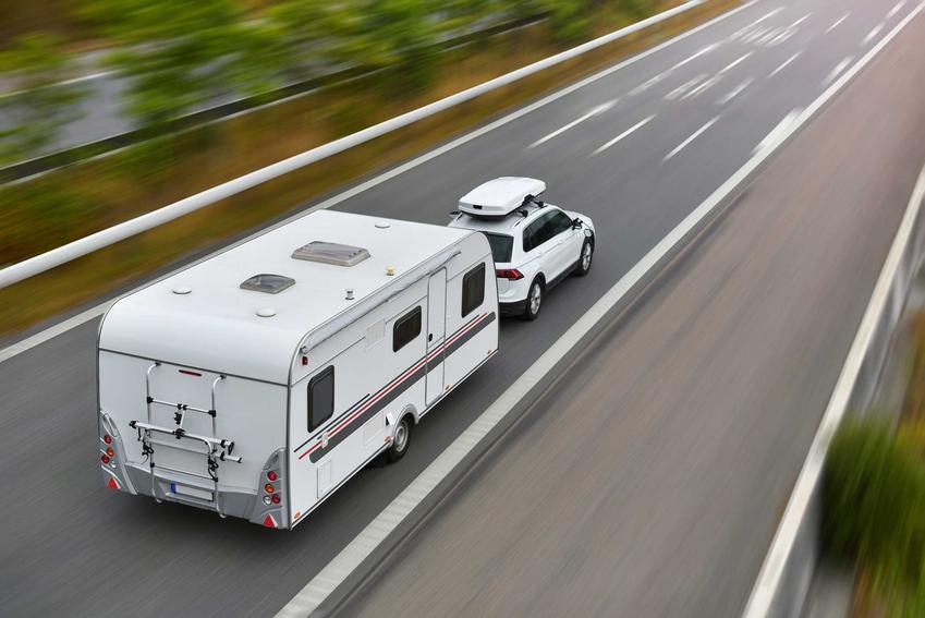 Samochód z przyczepą kempingową na autostradzie, a także ceny przyczep kempingowych, ile kosztują nowe i używane przyczepy