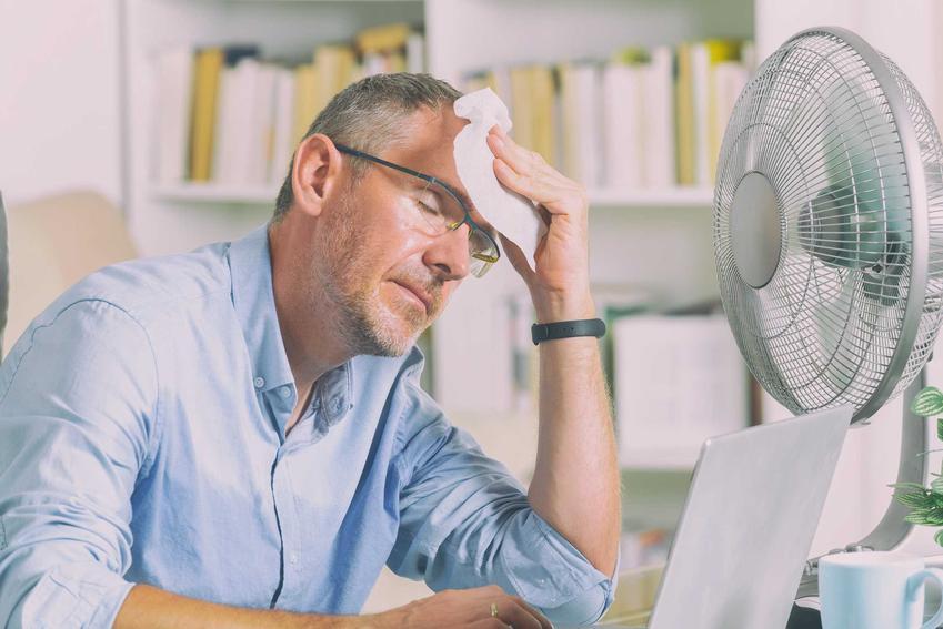 Meżczyzna męczący się z powodu upału w gabinecie, a także informacje i wskazówki, jak schłodzić dom bez klimatyzacji