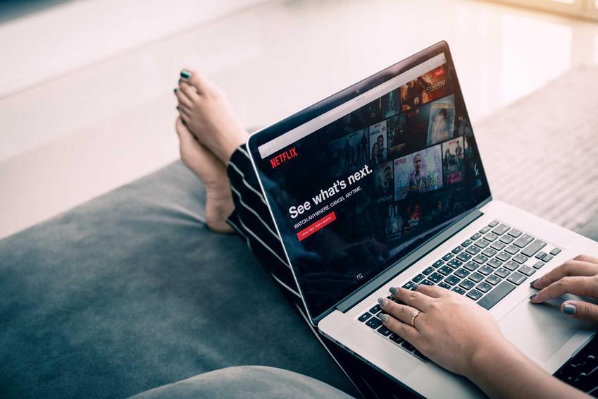 Kobieta oglądająca filmy na Netflixie, a także cennik Netflix, czyli aktualne ceny abonamentów w serwisie Netflix