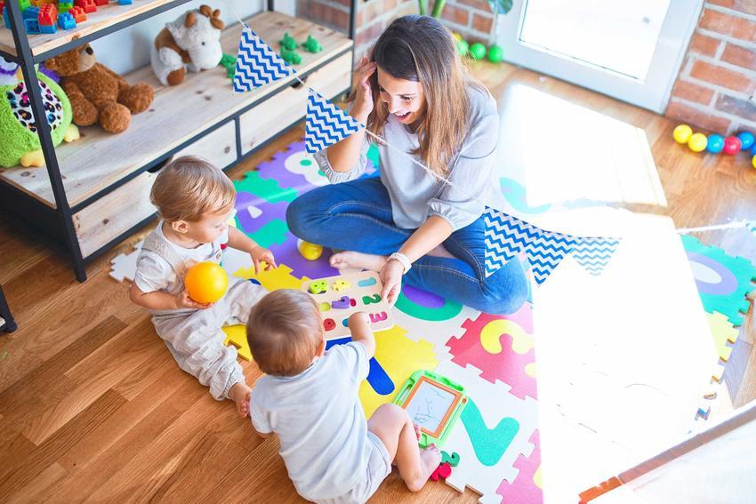 Niania bawiąca się z dziećmi w pokoju dziecięcym, a także informacje o umowie uaktywniającej z nianią, przepisy i prawo