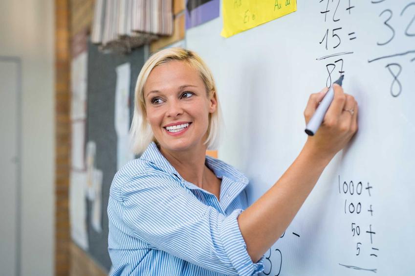 Nauczycielka tłumacząca dzieciom na lekcji matematyki, a także zarobki nauczycieli, stawki i możliwe dodatki krok po kroku