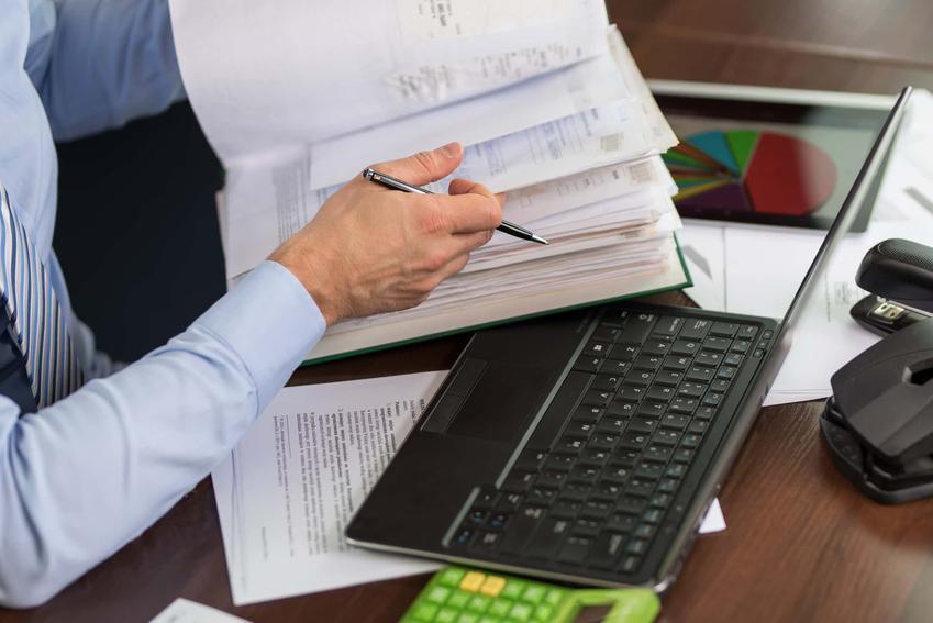 Mężczyzna w koszuli siedzi przy biurku przeglądając dokumenty, co to jest operat ppoż i komu zlecić jego wykonanie, operat przeciwpożarowy dla odpadów