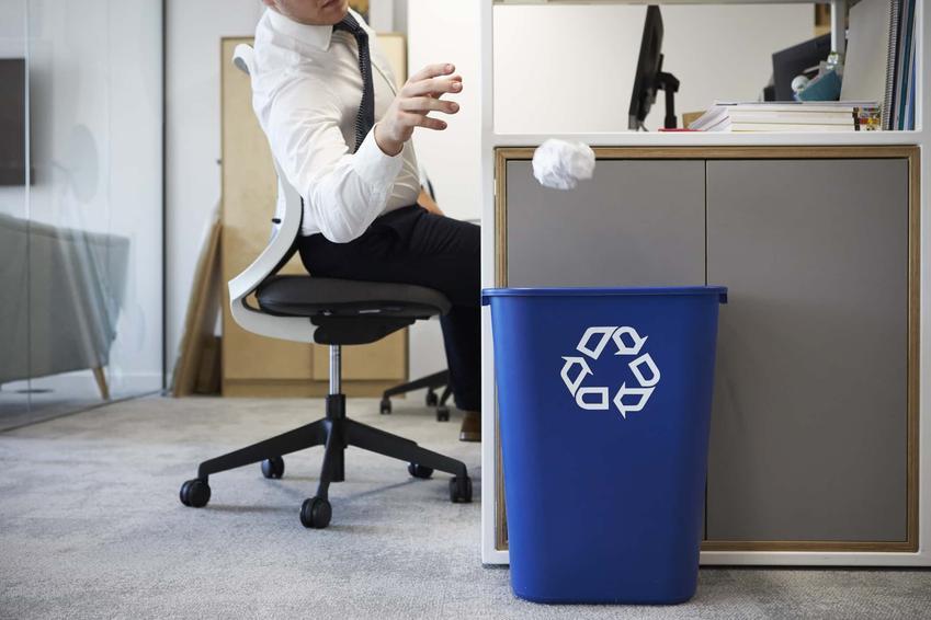 Mężczyzna siedzący przy biurku wrzuca do kosza zgnieciony papier, zezwolenie na składowanie odpadów i ich przetwarzanie, wymagania przeciwpożarowe dla odpadów