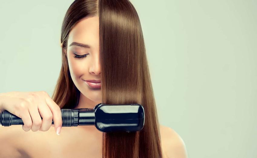Uśmiechnięta kobieta rozczesuje pasmo włosów, kobieta o gładkich i prostych włosach, kto może wykonać zabieg keratynowego prostowania włosów