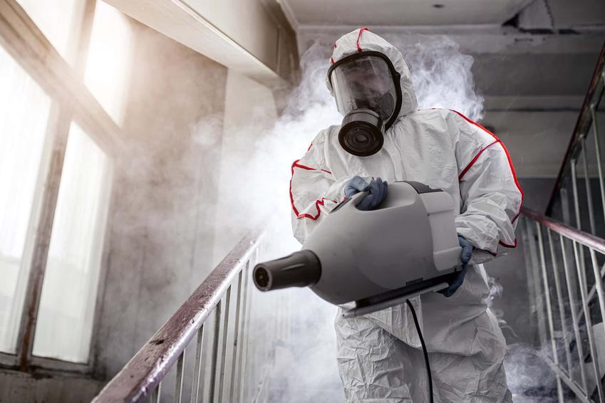 Mężczyzna w kombinezonie i masce ochronnej ozonuje pomieszczenie, czy ozonowanie jest bezpieczne dla ludzi, czy ozonowanie działa