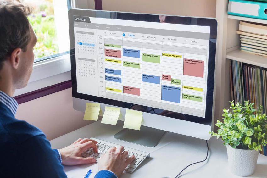 Mężczyzna siedzi przed komputerem, na którym naklejone są małe żółte karteczki, jak zaplanować pracę w trybie zadaniowym, czyli jak zarządzać czasie podczas pracy zadaniowej