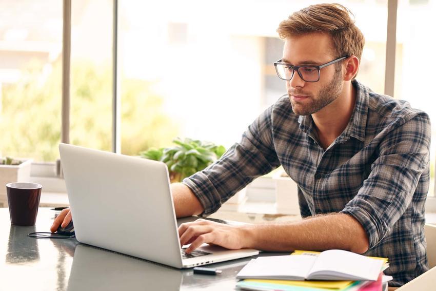 Mężczyzna w okularach siedzi przed laptopem, jak starać się o dofinansowanie do okularów używanych w pracy