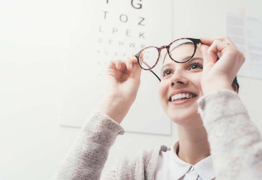 Uśmiechnięta młoda kobieta patrzy przez okulary trzymane w ręku przed twarzą, czy pracodawca powinien zlecać badania okresowe pracowników, wada wzroku a praca przed komputerem