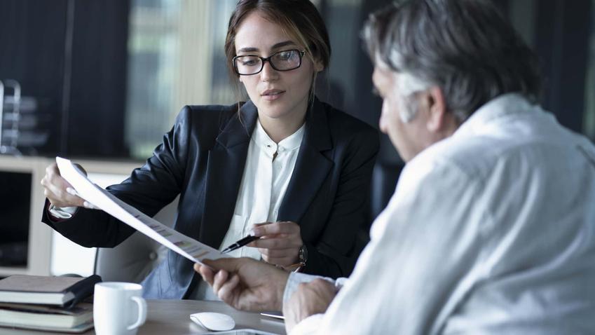 Kobieta w okularach pokazuje starszemu mężczyźnie dokumenty, umowa o pracę a wypowiedzenie, kiedy można wypowiedzieć umowę