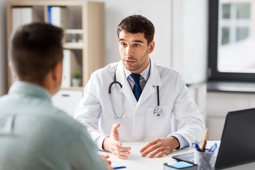 Mężczyzna siedzi w gabinecie lekarskim, doktor tłumaczy coś pacjentowi, wazektomia jako zabieg urologiczny dla mężczyzn, czy wazektomia jest zabiegiem odwracalnym