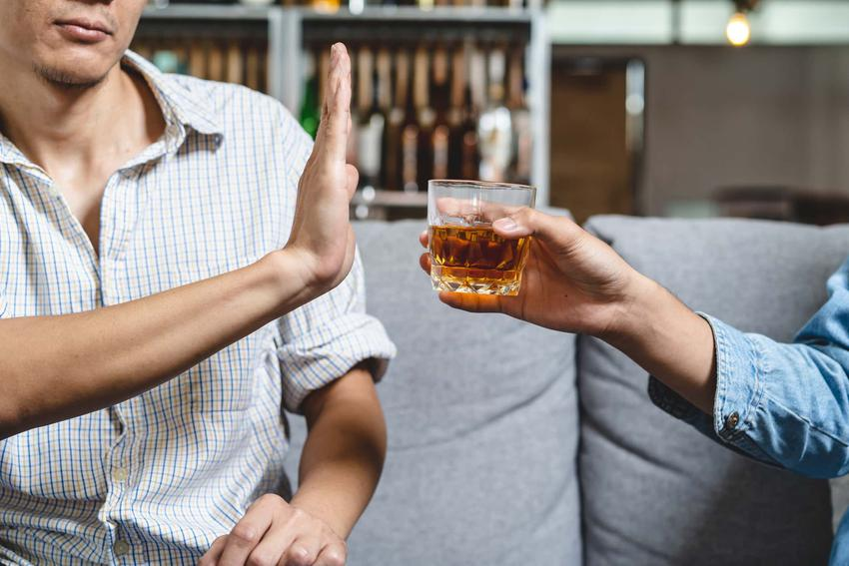 Dwóch mężczyzn siedzi na kanapie z których jeden gestem ręki odmawia przyjęcia szklanki z alkoholem
