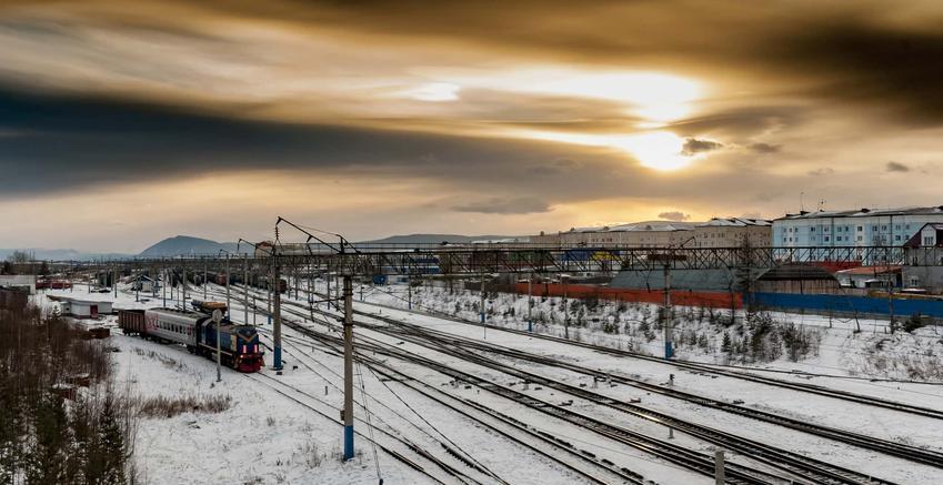 Zaśnieżony krajobraz zachodzące słońce i tory kolejowe, bilety na podróż drugą klasą kolei trassyberyjskiej