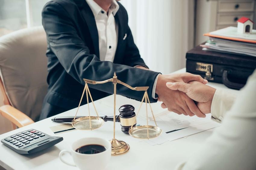 Dwie osoby podają sobie dłonie siedząc na przeciwko siebie po dwóch stronach biurka,Przedstawicielstwo ustawowe a pełnomocnictwo, przedstawicielstwo ustawowe a akty prawne