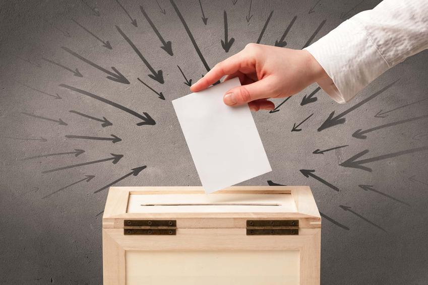 Dłoń kobiety wrzuca kartę do głosowania do drewnianej urny, cel zwołania referendum w gminie, powiatowe i wojewódzkie referendum