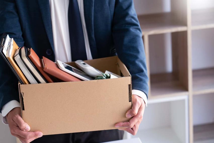 Mężczyzna w garniturze stoi w biurze z kartonem w rękach, mężczyzna odchodzi z pracy, skócenie okresu wypowiedzenia a odszkodowanie