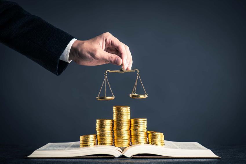 Stosy złotych monet ułożone na otwartej książce, jak uzupełnić formularz o zwolnienie z kosztów sądowych