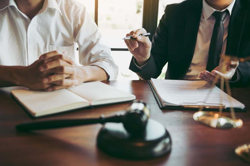 Dwóch mężczyzn siedzi przy biurku przeglądając dokumenty, wzór co powinien zawierać wniosek o zwolnienie z kosztów sądowych, dane jakie powinien posiadać wniosek o umorzenie kosztów sądowych