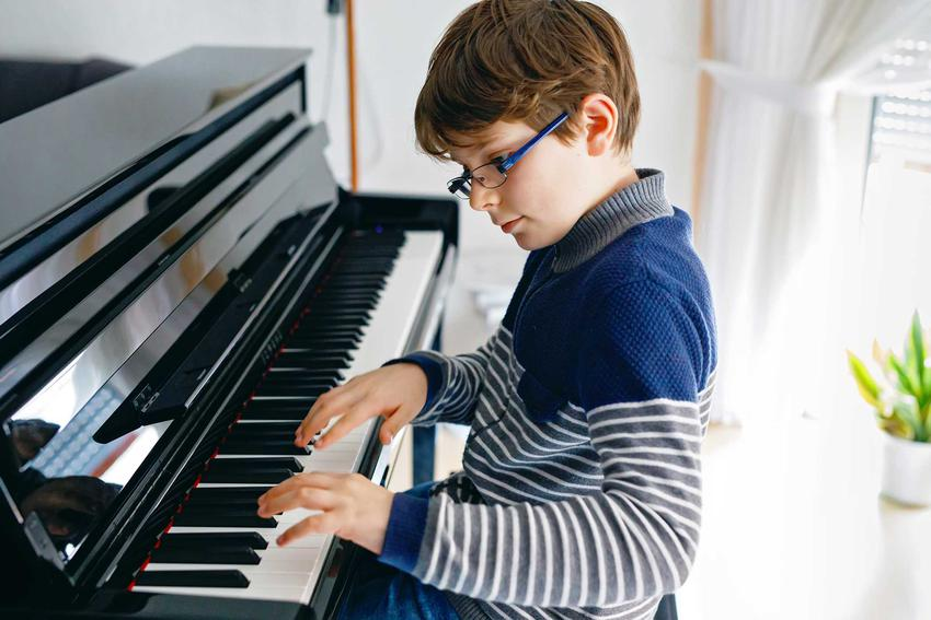 Chłopiec ćwiczący grę na pianinie, a także jakie są ceny pianina u różnych producentów