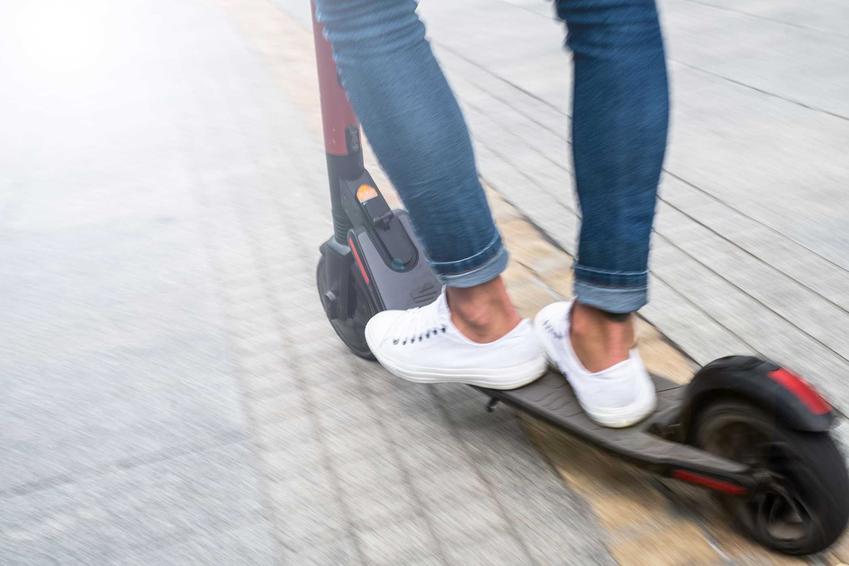 Kobieta jadąca na hulajnodze elektrycznej, a także ile kosztuje hulajnoga elektryczna - ceny u róznych producentów