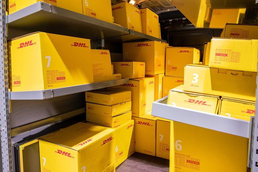 Paczki nadane przez DHL w samochodzie dostawczym, a także cennik DHL oraz ceny usług kurierskich w tej firmie