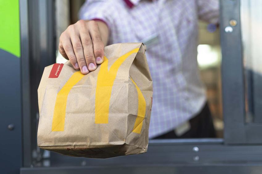 Pracownik McDonalds obsługuje klienta McDrive, pracownik McDonalds trzyma wyciagniętą rękę z posiłkiem w stronę klienta, ile kalorii mają sałatki w McDonalds