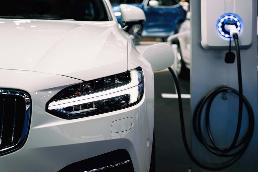 Biały samochód elektryczny podłączony do ładowania, ile kosztuje utrzymanie samochodu elektrycznego i czy warto kupić auto elektryczne