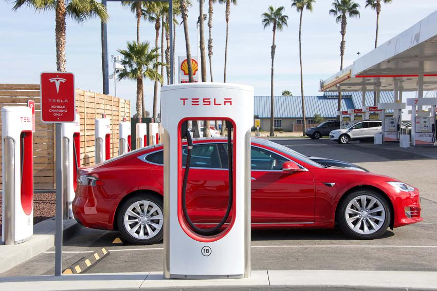 Czerwona Tesla podłączona do stacji ładowania, co może się zepsuć w Tesli, czy samochody elektryczne są ekologiczne