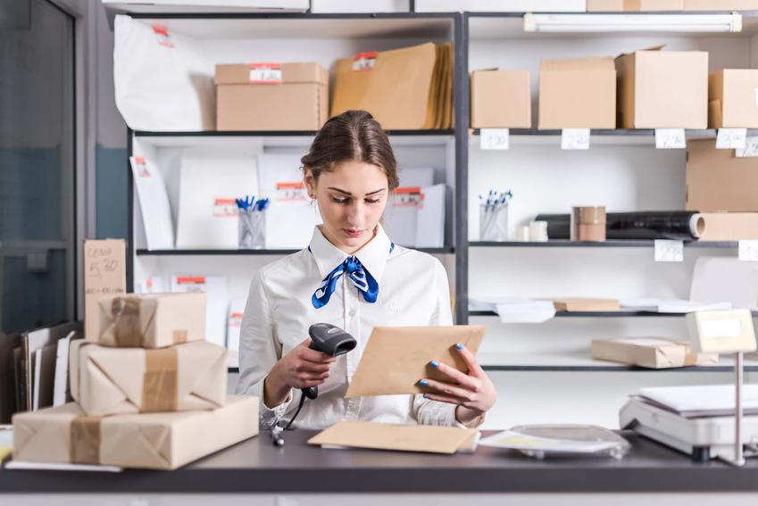 Kobieta w pocztowym mundurku skanuje paczkę, jakie są ceny przesyłek krajowych i zagranicznych, list ekonomiczny czy priorytetowy