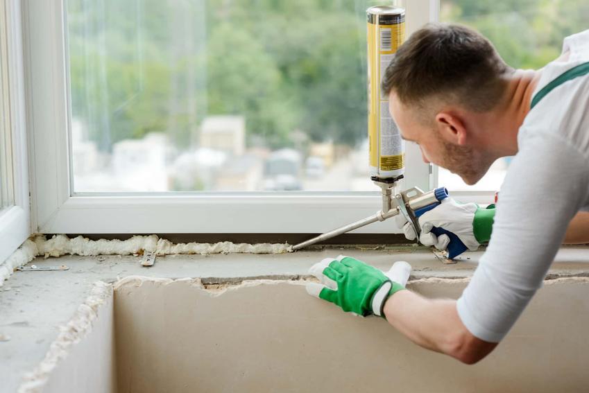Mężczyzna wyciska piankę montażową w okolicy okna, robotnik budowlanny remontuje dom, jakie są ceny pianek montażowych w marketach