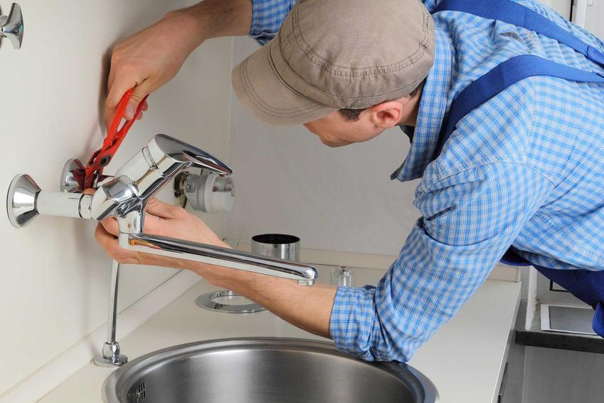 Mężczyzna montujący baterię w kuchni, a także samodzielny montaż baterii kuchennej krok po kroku, czyli jak zamontować baterię