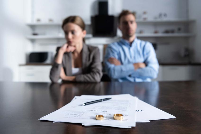 Mężczyzna i kobieta siedzą obok siebie w złym nastroju, a na stole dokumenty rozwodowe i obrączki, wyrok rozwodowy wskazujący na winę jednego z małżonków