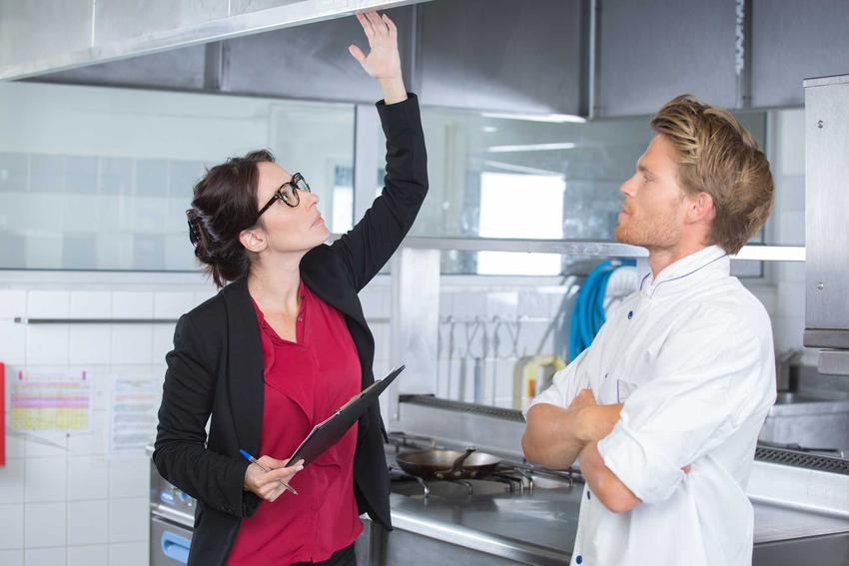 Kontrola sanepidu w restauracji przeprowadzana przez kobietę w eleganckiej garsonce i bluzce, sprawdzającą jakość umeblowania w towarzystwie stojącego obok kucharza