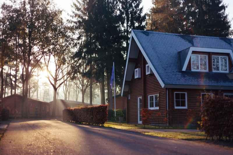 Niewielki dom z ciemną elewacją na skraju drogi objęty hipoteką, a także informacje o hipotece na dom krok po kroku - jak założyć, jak spłacić, jak ją zdąć