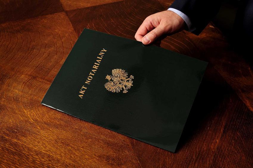Akt notarialny w skórzanej teczce leżący na stole. Akt notarialny jest podstawą do zmiany w księgach wieczystych, bez niego nie możesz przystąpić do składania wniosku w sądzie.
