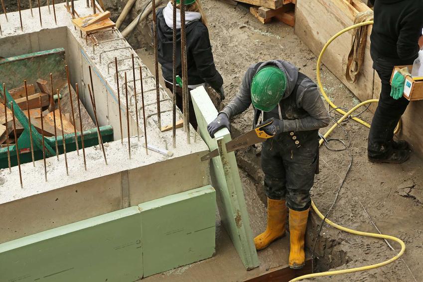 Robotnik ociepla fundamenty za pomocą płyt ze styroduru