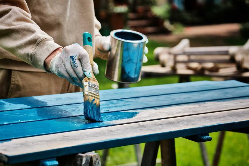 Malowanie starego stołu farbą akrylową o niebieskim odcieniu w ogrodzie przez mężczyznę w szarej bluzie