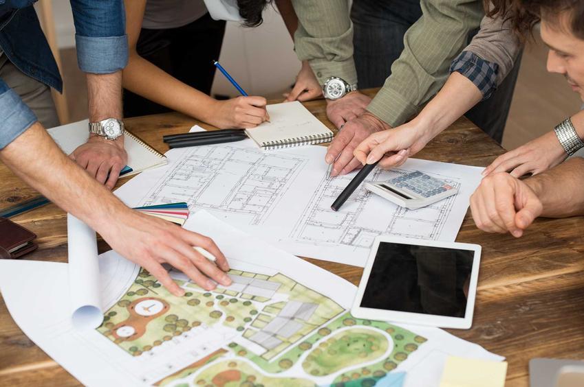 Grupa młodych architektów pochyla się nad projektem przy stole zastawionym dokumentami, wydrukami i notatkami