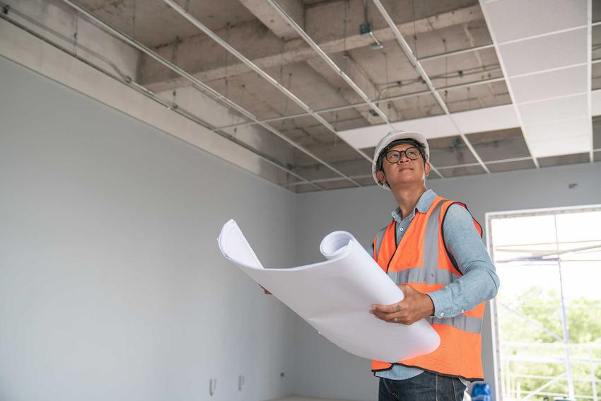 Odawanie budynku do użytkowania przez inżyniera trzymającego w dłoniach projekt, stojącego wewnątrz domu na tle okna