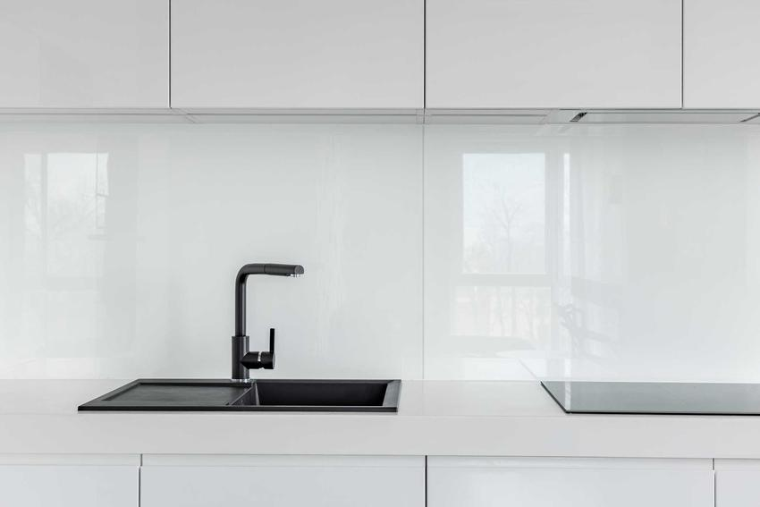 Szkło w kuchni zamontowane nad zlewem i kranem pod szafkami kuchennymi, meble i szklane płytki utrzymane w białym kolorze