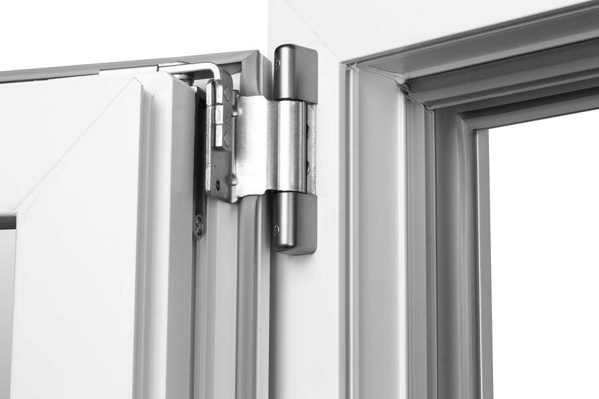 Zawiasy nowszego typu w drzwiach zewnętrznych lub wewnętrznych na białych drzwiach przy framudze