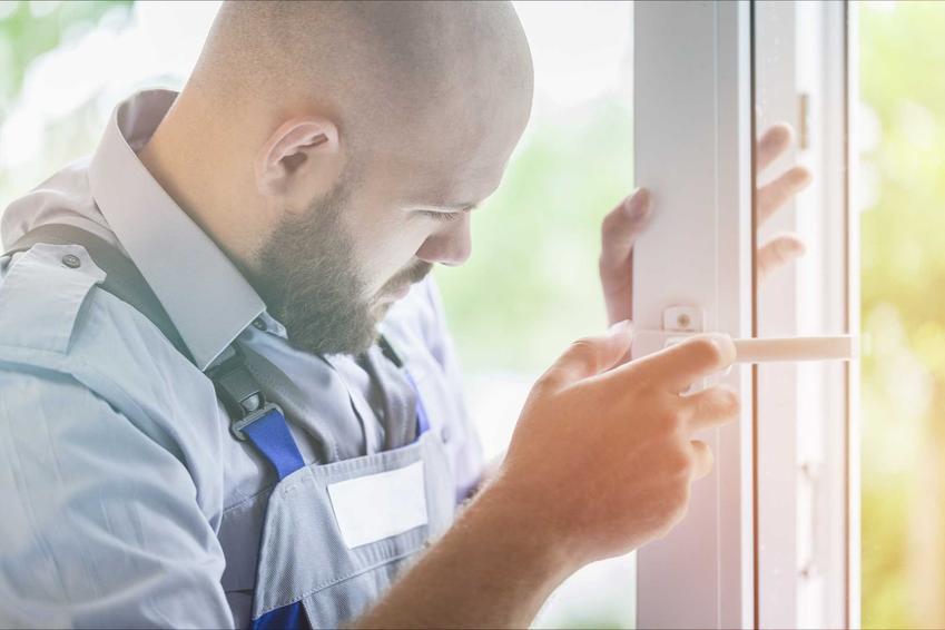 Regulacja drzwi balkonowych wykonywana przez mężczyznę z brodą w ubraniu roboczym stojącym przy oknie, zza którego widać zieleń
